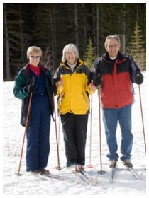 Three people posing wearing cross country skis in winter