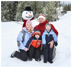 Family of four posing next to a snowman