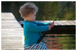 Young child sitting on a dock holding a fishing pole