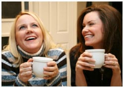 Two women laughing and drinking coffee