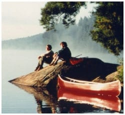 Man and woman sitting on a rock looking over a lake with a canoe in the foreground.