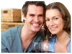 A couple posing for a picture with wine glasses in hand