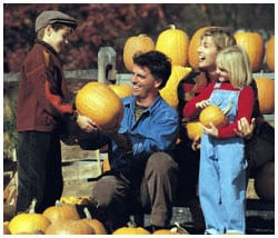 Family of four picking out pumpkins at a pumpkin patch.