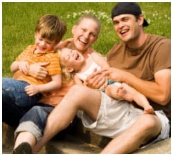 Family of four sitting in the grass posing for a picture