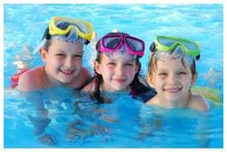Three kids in a swimming pool wearing swimming goggles.