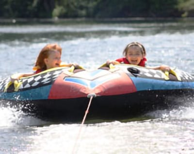 Two girls riding on a tube at the lake.