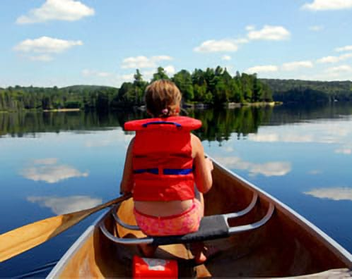 Girl sitting in a canoe overlooking Stoney Lake