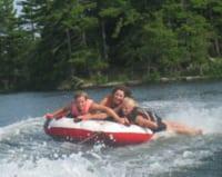 Three women riding a tube at the lake