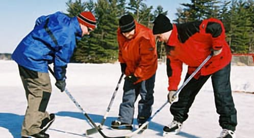 Three people playing ice hockey